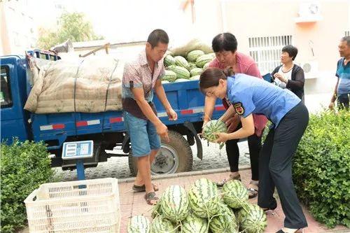 """执法人员为瓜农安排摊位,帮助他们销售""""岳里西瓜"""""""